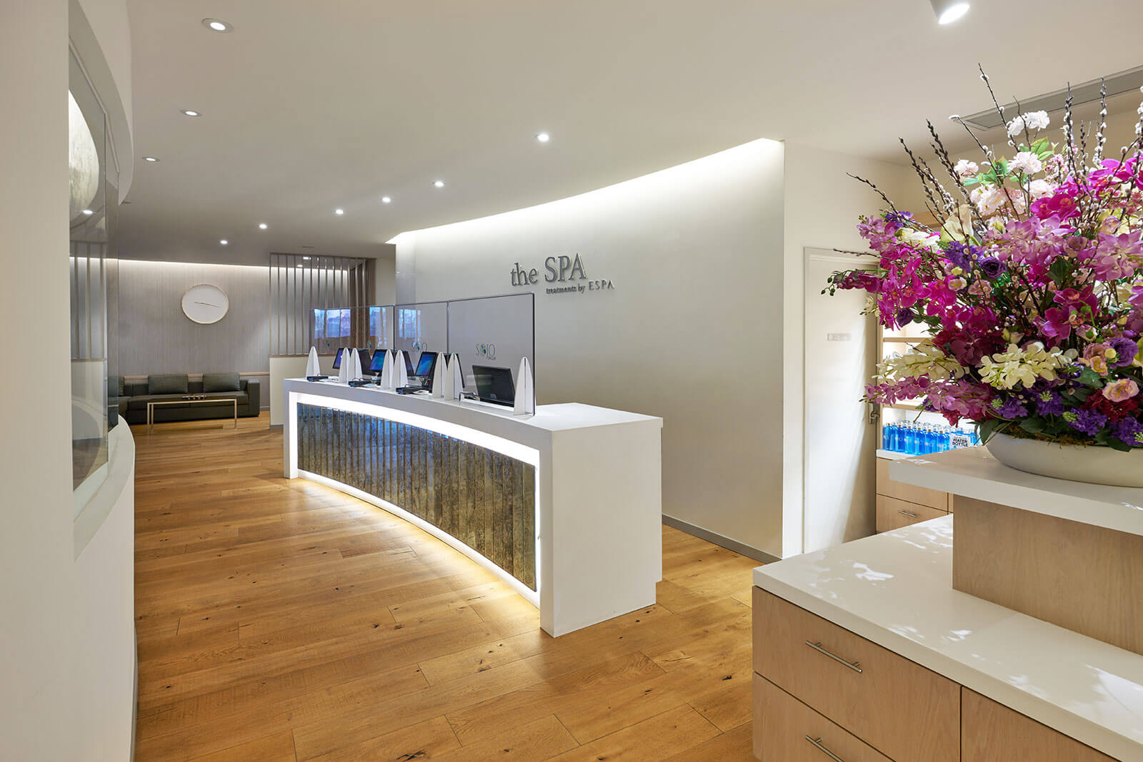 The spa reception area including a front desk, hardwood floors, and waiting area in the background.